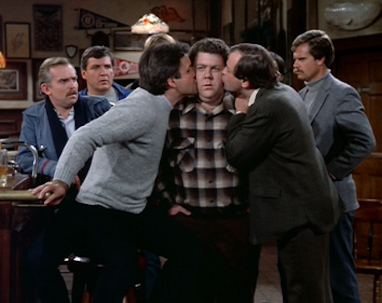 Two_guys_kissing_Norm's_cheeks_in_%22The_Boys_in_the_Bar%22